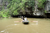 Getting ready to go under a limestone cave on Tam Coc river, Ninh Binh, Vietnam