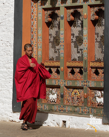 Buddhist Monk next to a colourful window at Punakha Dzong, Bhutan