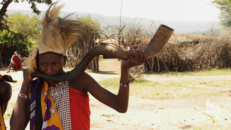 Maasai warrior blows a trumpet made from the horn of the greater kudu to signal capture of the lion