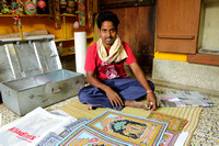 Raghurajpur artisan showing all the Patta Chitra paintings from his trunk box