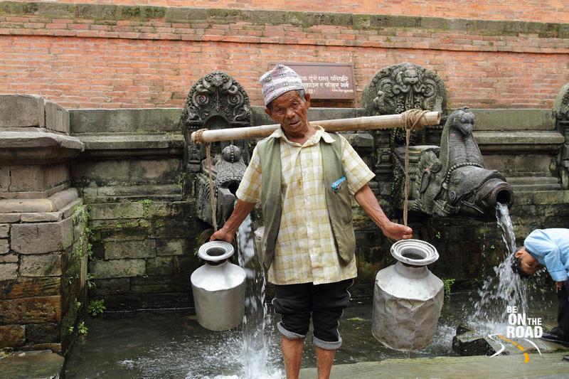 Local Nepali Gentleman filling water at a gargoyle in Patan
