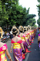 Line of colorfully dressed Balinese women walk on the streets as part of a temple procession