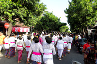 Traditionally dressed Balinese people walk as part of a temple procession