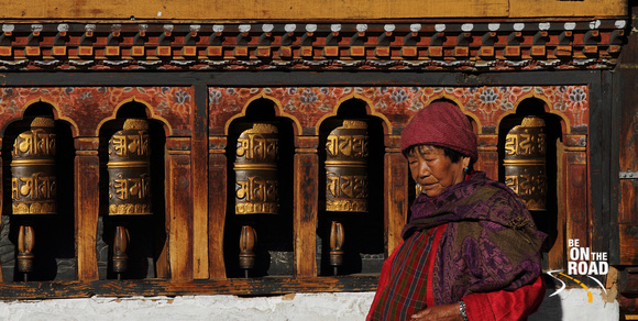 Buddhist woman in front of the prayer wheels of Changangkha Lakhang, Thimphu, Bhutan
