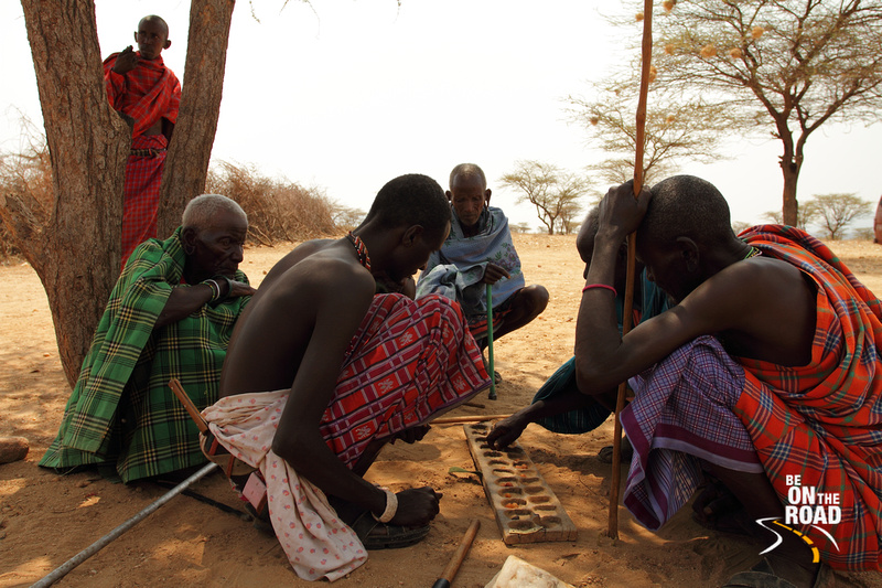 Samburu Elders huddle together under a tree to play a game
