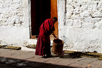 Buddhist Monk cleaning the brass lamps at Trongsa Dzong
