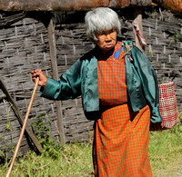 An Elderly Bhutanese Woman walks in Trongsa, Bhutan