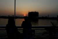 Sun sets by a high rise building by the Mekong river at Phnom Penh